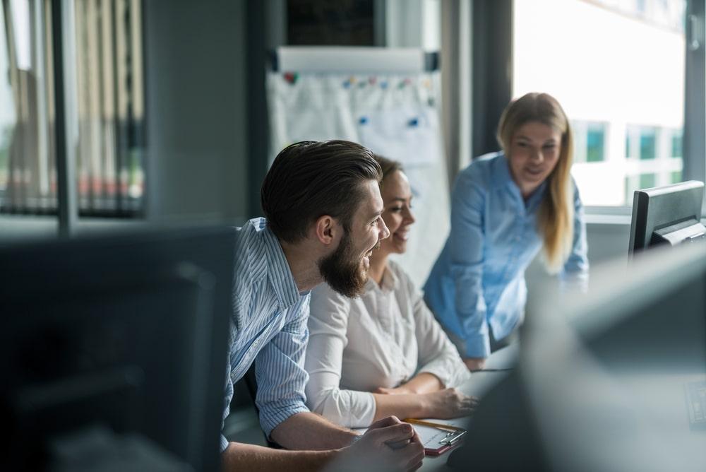 Drie mensen aan het werk in een kantoor